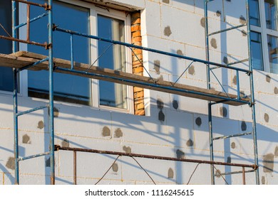 Scaffold on house, renovation. House for renovation with the scaffolding for workers on building, close up