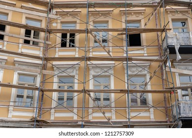 Scaffold on house, renovation. Scaffolding on building, beige wall and window. Scaffolding system in construction.
