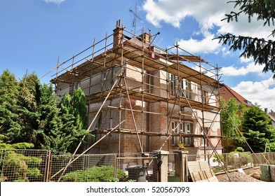 Scaffold on house, renovation. Scaffolding on building with old roof and material on ground.