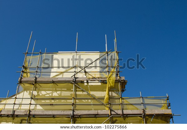 A scaffold structure made from bars and planks with a yellow safety netting around a beige chimney against a clear blue sky.