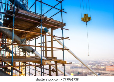 Scaffolding at altitude. High-altitude work. Crane hook. Lifting of building materials.