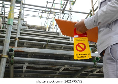 Scaffolding inspectors or supervisor are checking scaffolding by using checklists and tags are for hanging detailing labels on scaffolding in onshore oil and gas plant, chemicals plant or power plant