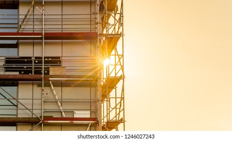 Scaffolding on a construction site. Commercial building with sunbeams in the back light