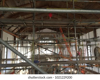 Scaffolding poles and boards inside old chapel