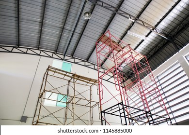 Scaffolding for replacing light bulbs in high roofing factory.