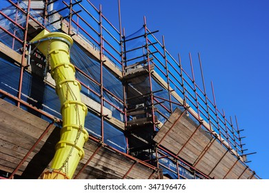 Scaffolding with slide for debris and rubble