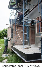 scaffolding steel for small building construction:male worker plasterering cement wall