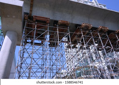 Scaffolding for support underneath sky train concrete bridge  while constrution on process for safety workplace, clear blue sky and building background.
