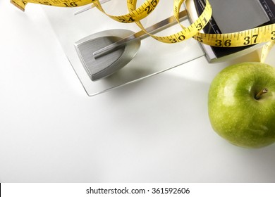 Scale with apple and tape measure isolated. Concept health, diet and nutrition. Horizontal composition. Top view
