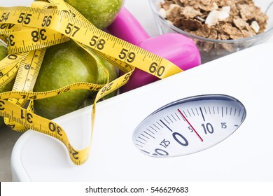 scale with cereals, fruit, weight and tape measure and concept of diet and healthy lifestyle