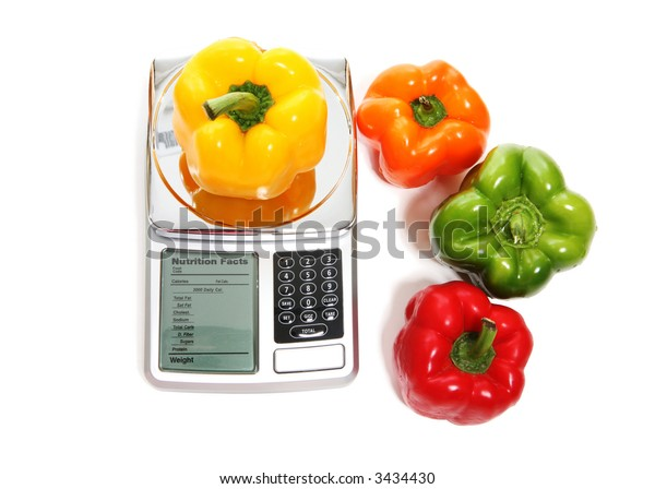 A scale with colorful peppers over white