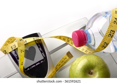 Scale with heart message with mineral water, apple and tape measure isolated. Concept health, diet and nutrition. Horizontal composition. Top view