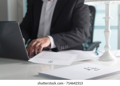 Scale and justice sign on pile of paper. Lawyer working in office. Attorney writing a legal document with laptop computer. Law firm and business concept.