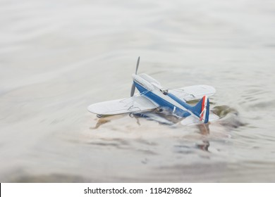 Scale model hydroairplane on the surface of water. The plane begins to drown after an unsuccessful landing. Copy space. Toy