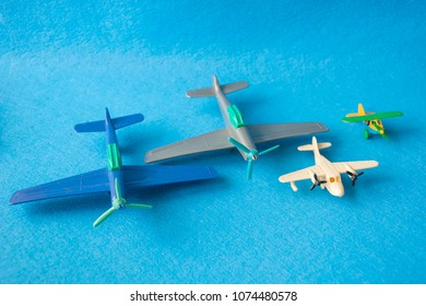 Scale models of colored small plastic toy planes. Macro photograph of midget aircrafts. Isolated on blue background