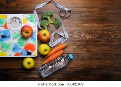 Scales, apples, water on the wooden background