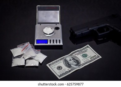 scales with cocaine, gun  and money on black table
