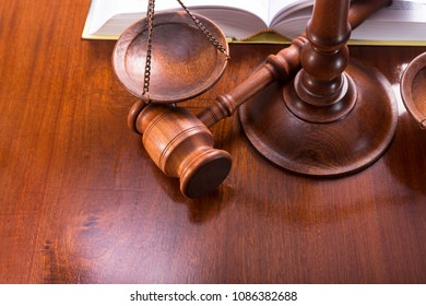 Scales with a gavel and a book on a lacquered table