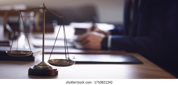 Scales of justice and blurred lawyer on background. Banner design