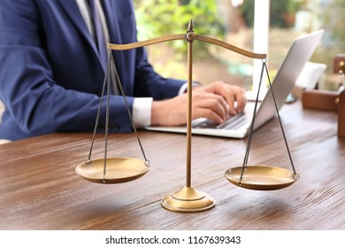 Scales of justice and blurred lawyer working with laptop on background