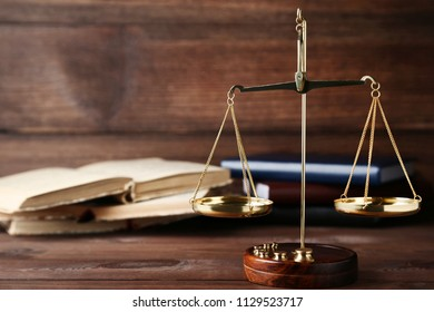 Scales of justice with books on brown wooden table