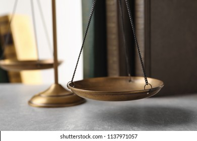 Scales of justice and books on table, closeup. Law concept