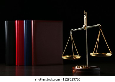Scales of justice with books on wooden table