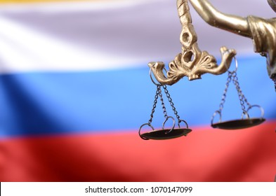 Scales of Justice, in front of the Russian flag in the background.