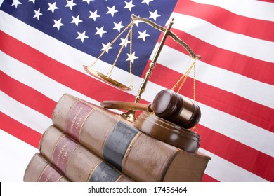 Scales of justice, gavel, stack of old law books with the American Flag in the background