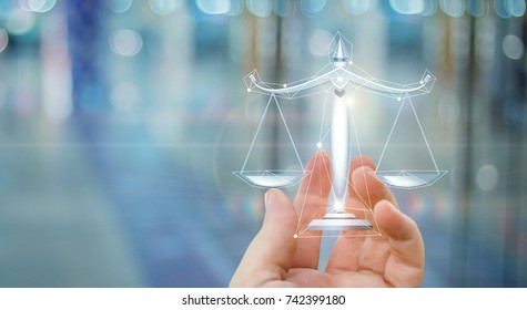 Scales of justice in hand on a blurred background.