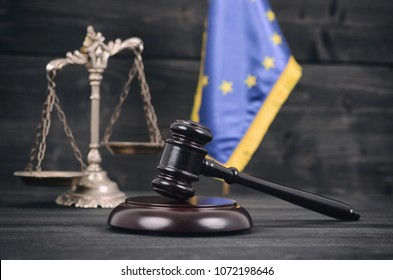 Scales of Justice, Judge Gavel and Flag of the European Union on a black wooden background.