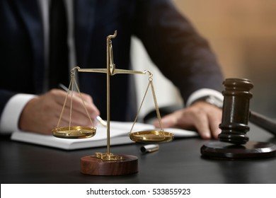 Scales of justice and judge gavel on table, closeup