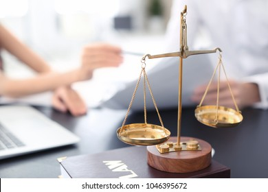 Scales of justice with juridical book on table in lawyer's office