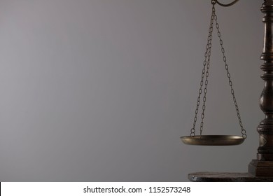 Scales of justice on gray background.
