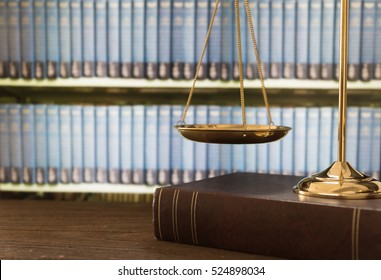 scales of justice on law books in library of law firm. legal education concept.