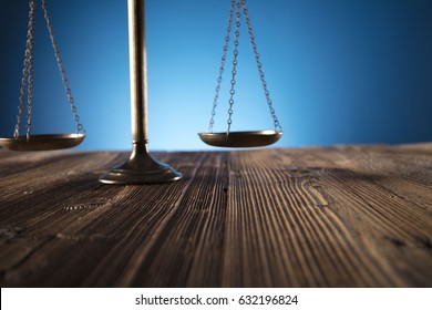 Scales of justice on old wooden table and blue background. Law theme and concept.