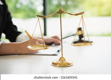 Scales of justice on white table background with female lawyers working at the law firms.