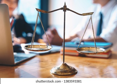 Scales of justice on wooden table background with Businesswoman and male lawyers discussing contract papers at the law firms. Legal law, lawyer, advice and justice concept.