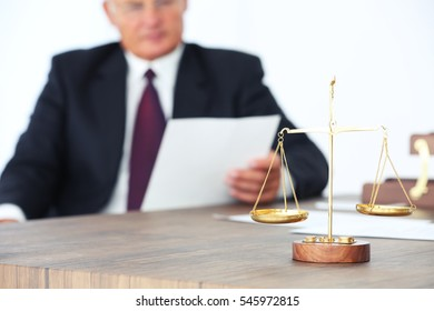 Scales of justice on wooden table and male lawyer on background