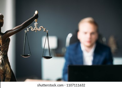 scales of justice. a young man is a lawyer, a judge, a prosecutor. concept of jurisprudence.