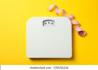Scales and measuring tape on yellow background. Weight loss concept