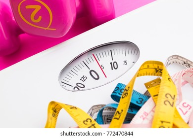 scales with measuring tapes and weights of the gym, concept of diet and beauty