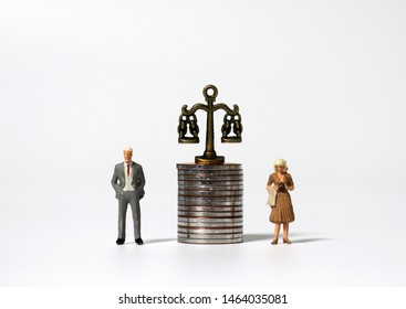 Scales and miniature people on a pile of coins.