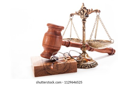 Scales of non-ferrous metal, a gavel and glasses on a white background