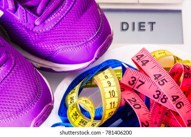 scales with runnig shoes and tape measure, diet and slimming concept