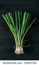 Scallions in the center on a black wooden background