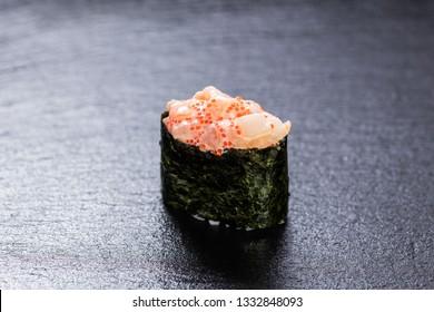 Scallop gunkanmaki over slate plate background