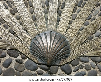Scallop shell embedded on street, typical way marking for the Camino de Santiago in Europe religious pilgrimage