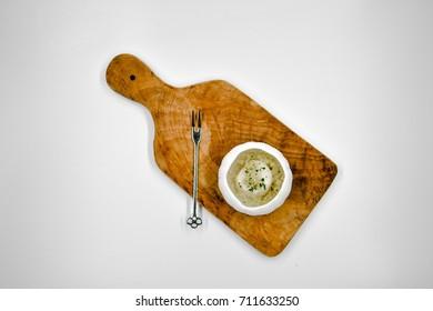 Scallops dish served in sea urchin (uni) shaped dish on bamboo.
