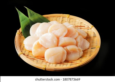 Scallops on bamboo colander and black background